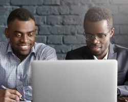 Two happy African colleagues using laptop. Manager in shirt showing presentation on notebook computer to his boss wearing suit and glasses, during meeting in modern office interior with brick walls